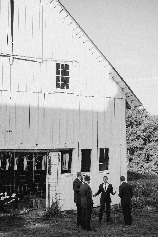 Groom and groomsmen standing in circle