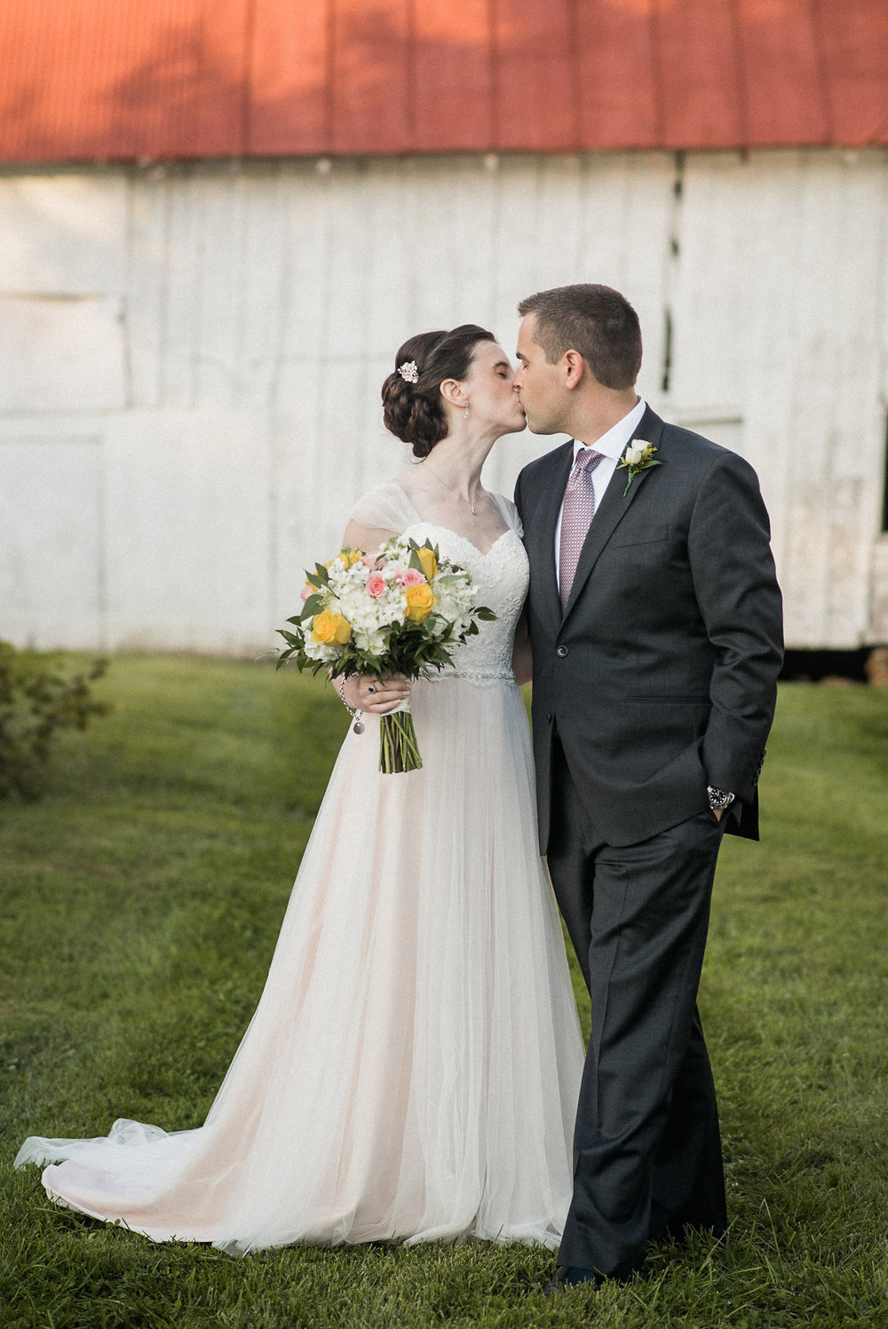 Bride and groom kiss in front of barn