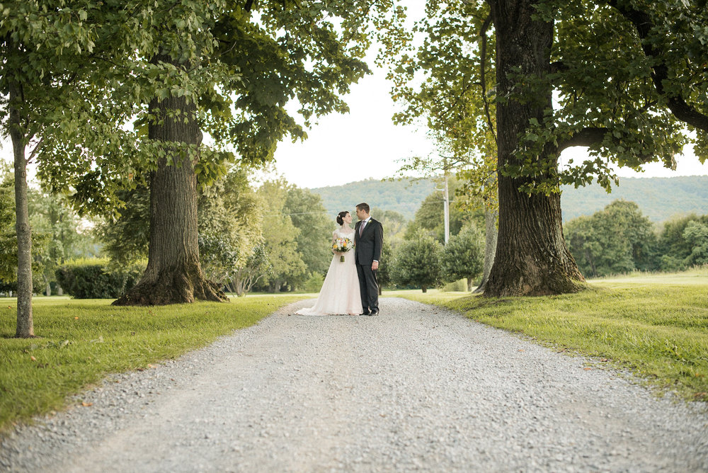 Bride and groom standing on country road
