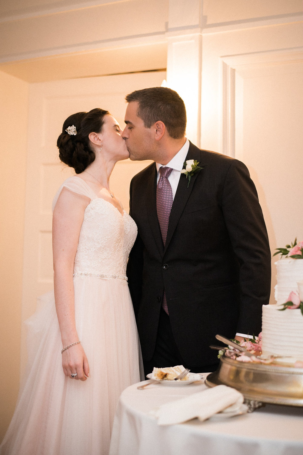 Bride and groom kissing beside cake