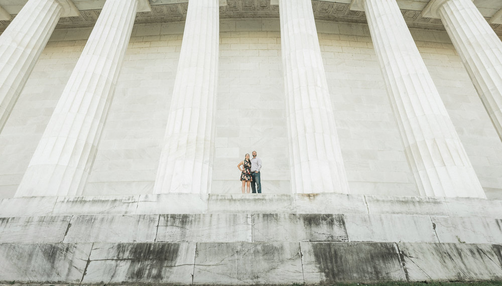 Couple standing between marble pillars