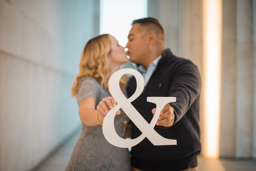 Engaged couple holding ampersand