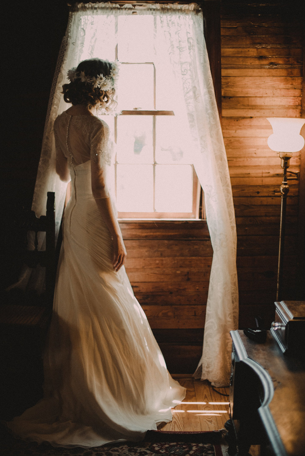 Bride looking out window before wedding