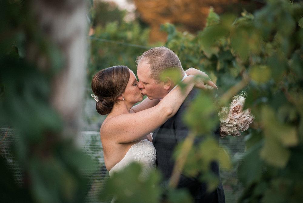 Couple seen through grapevine