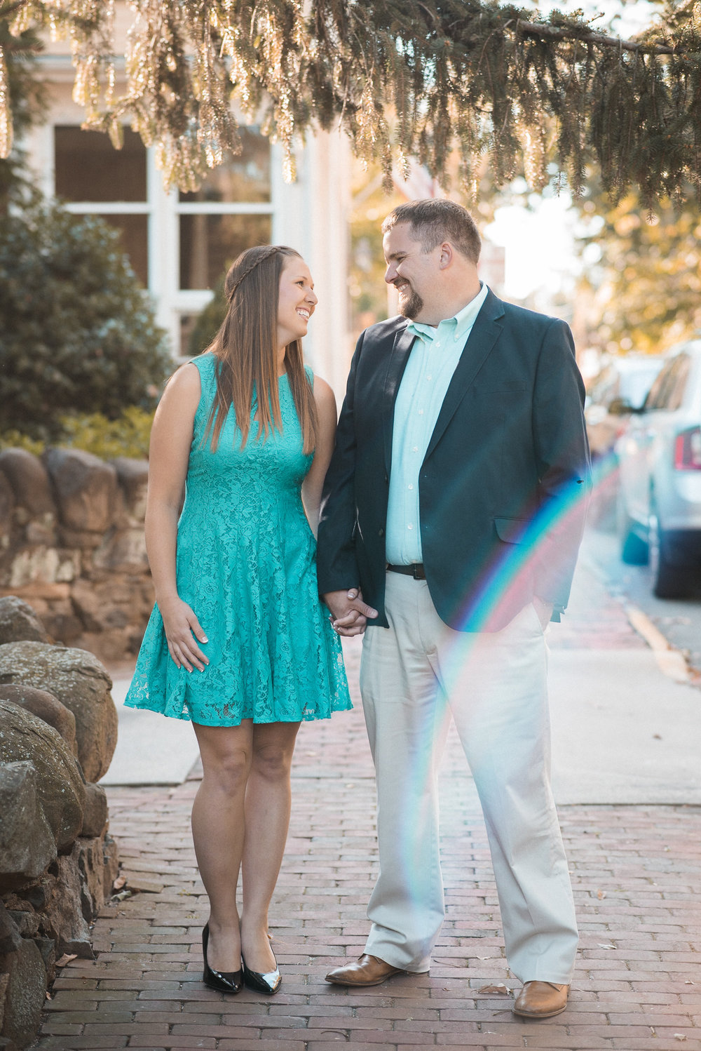 Couple standing on sidewalk holding hands
