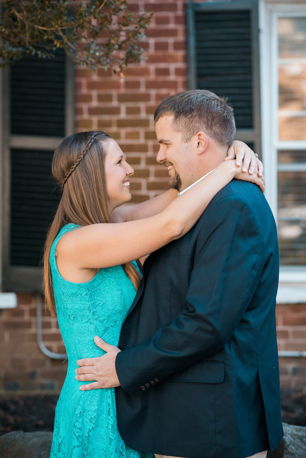 Couple hugging in front of brick wall