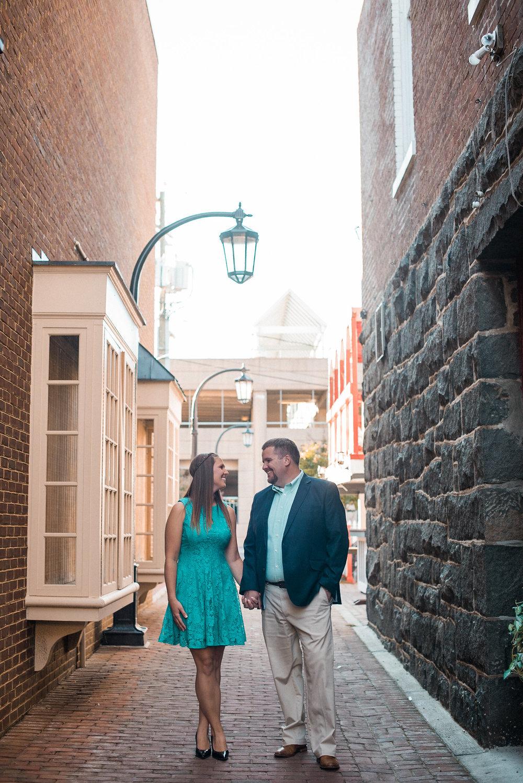 Couple standing in alleyway under lantern