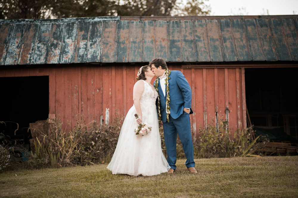 Couple kissing in front of red barn