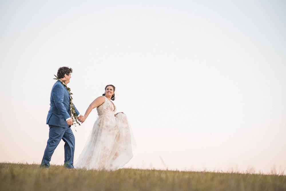 Bride leading groom across field