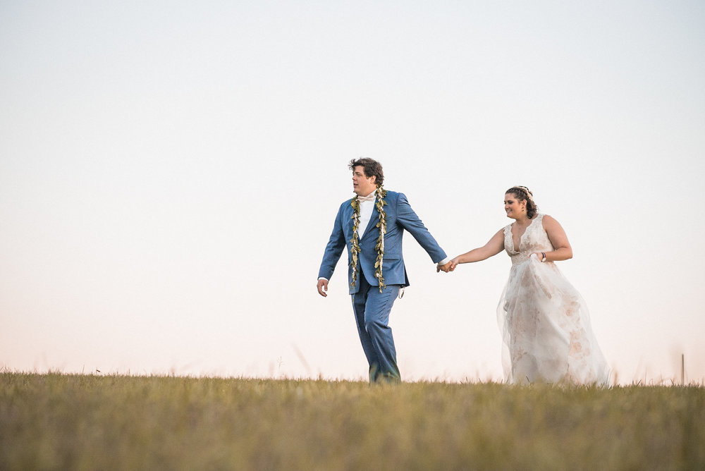 groom leading bride across field