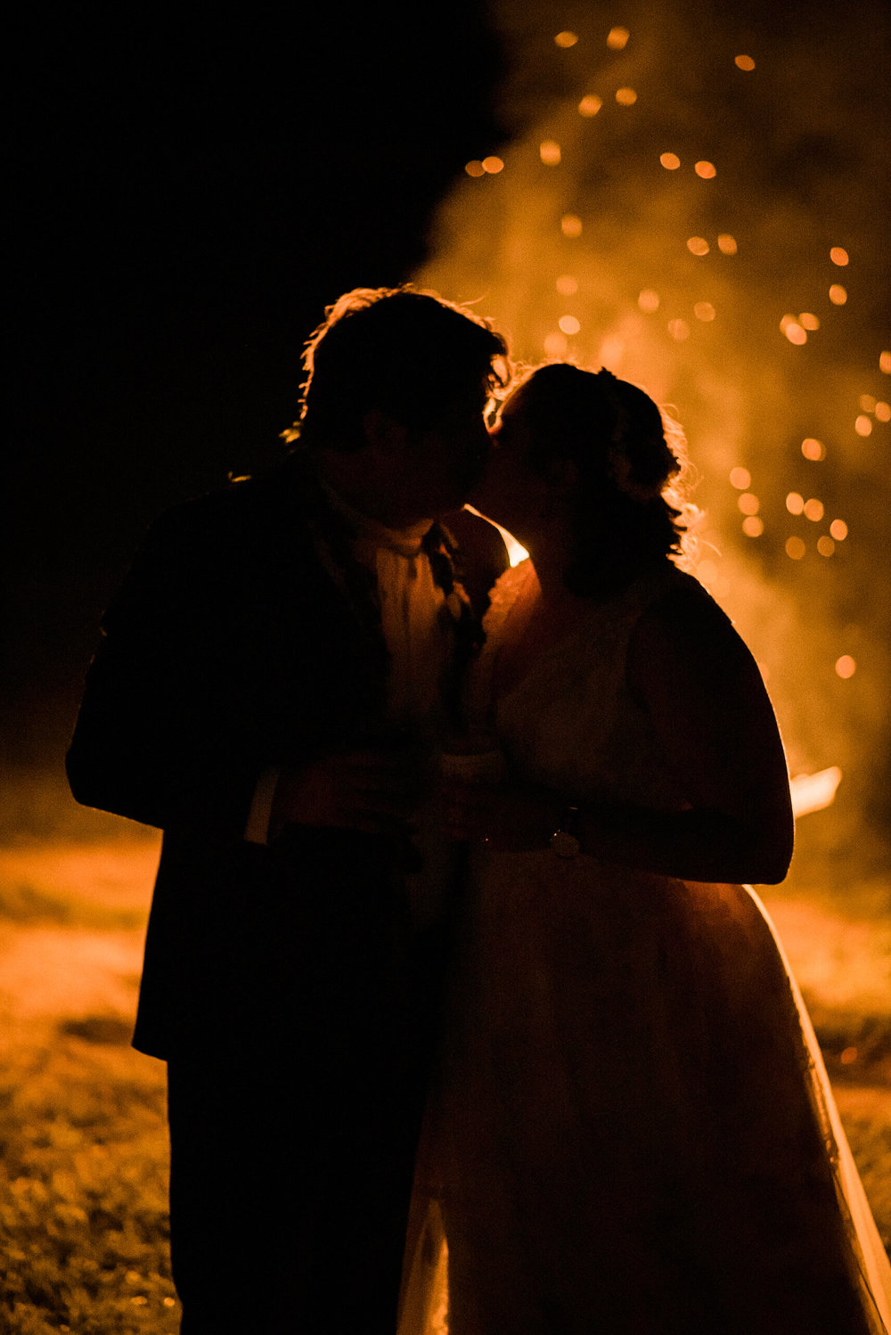 Bride and groom kissing by fire