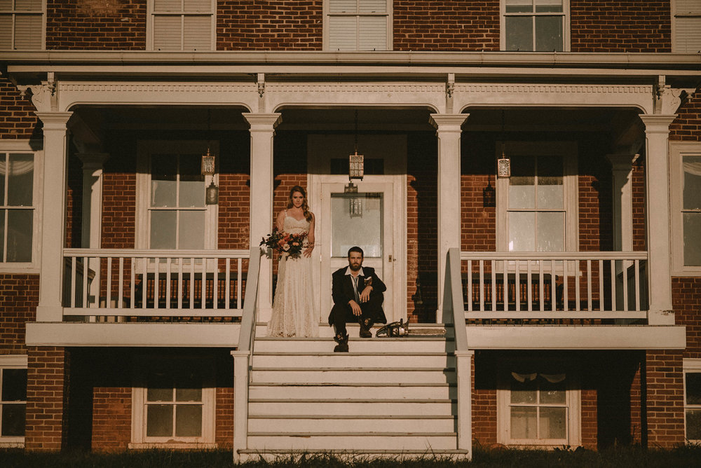 Bride and groom on porch of farmhouse