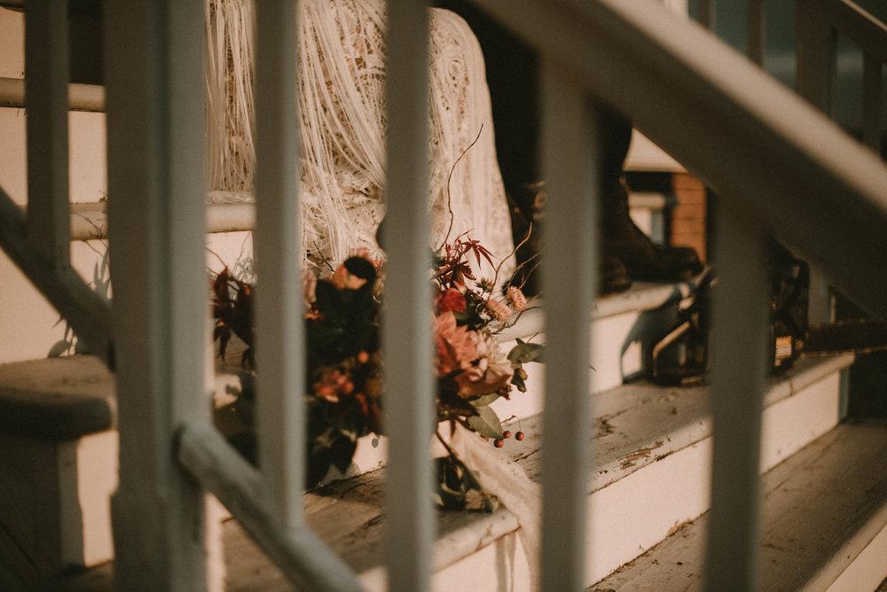 Flowers sitting on step beside bride