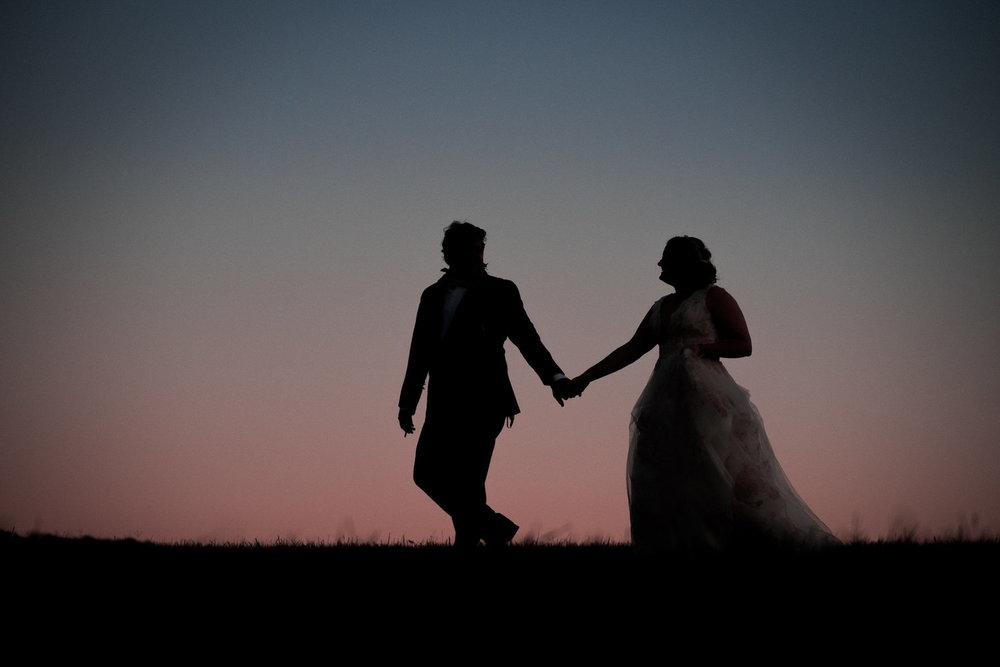 bride+and+groom+in+field+at+dusk.jpg