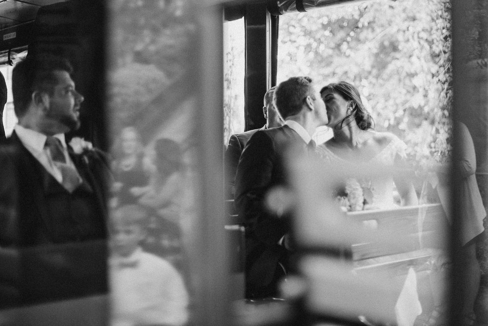 Bride and groom kiss on a trolley