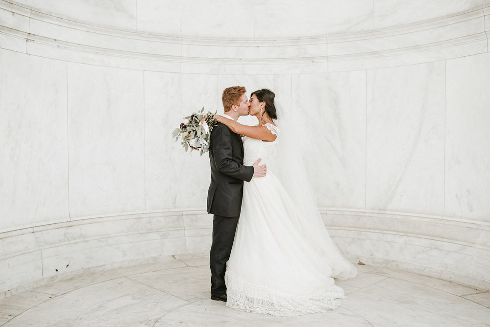 Bride and groom kissing in marble room