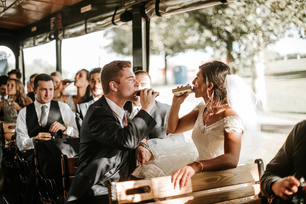 Bride and groom drinking from flasks