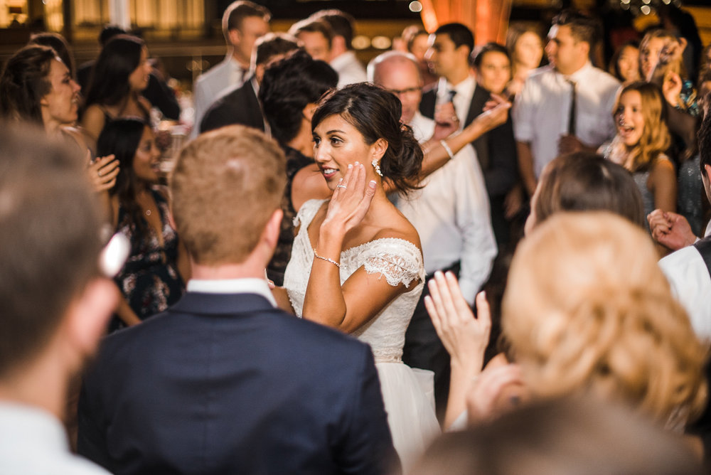Bride and groom dancing in crowd