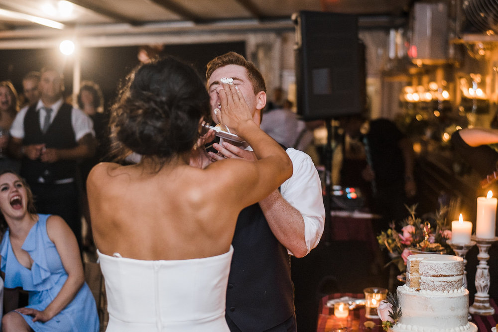 Bride smashing cake in groom's face