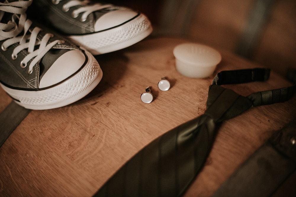 Converse and cuff links on wine barrel