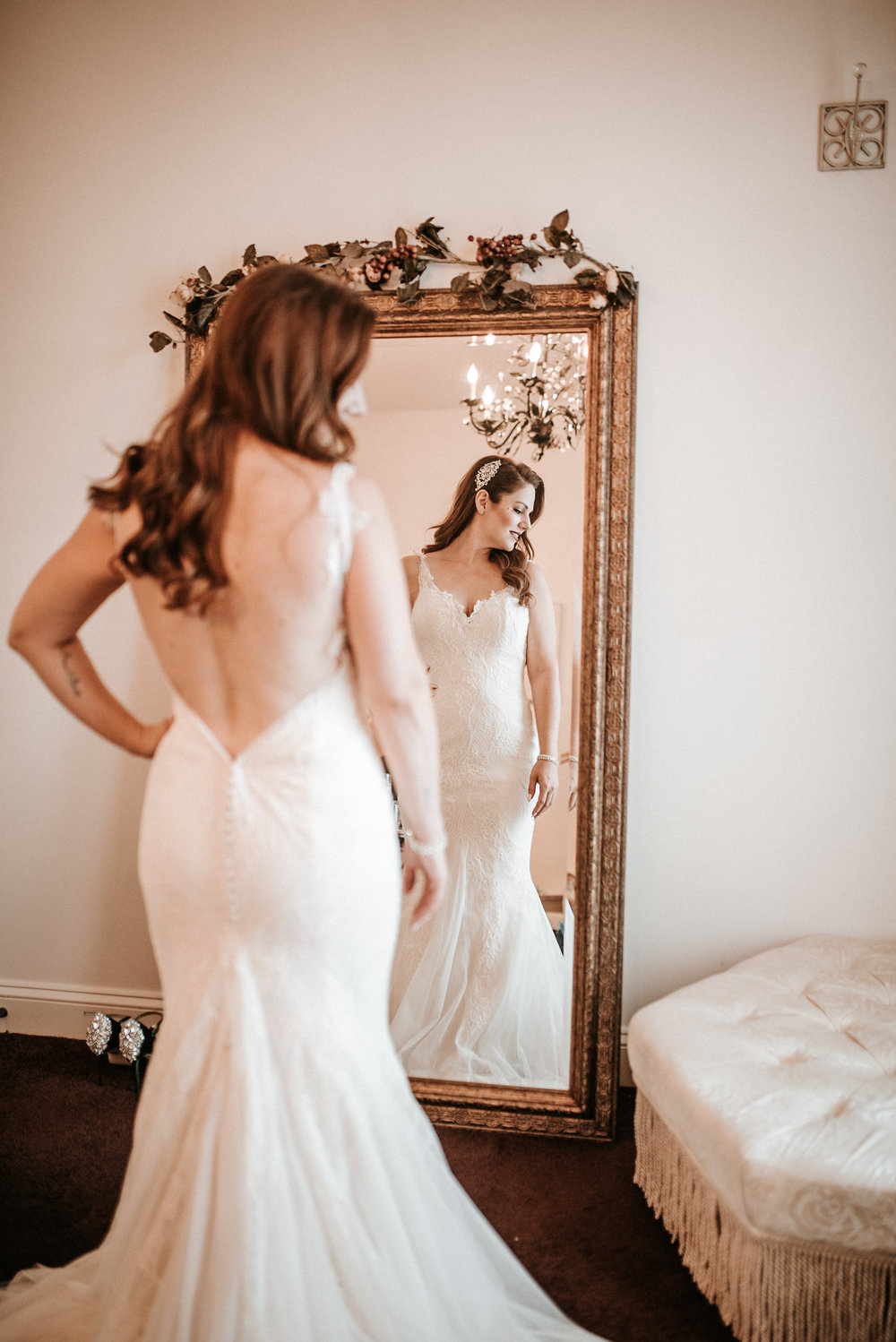 Bride looking over shoulder in front of mirror