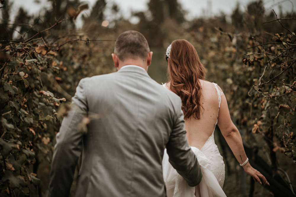 Bride and groom walking through vineyard