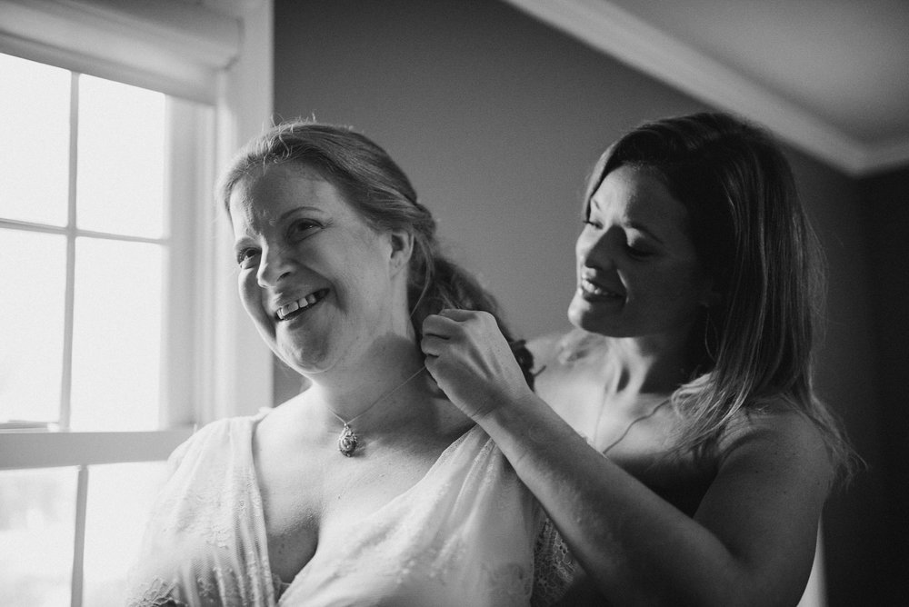 Bridesmaid putting necklace on bride