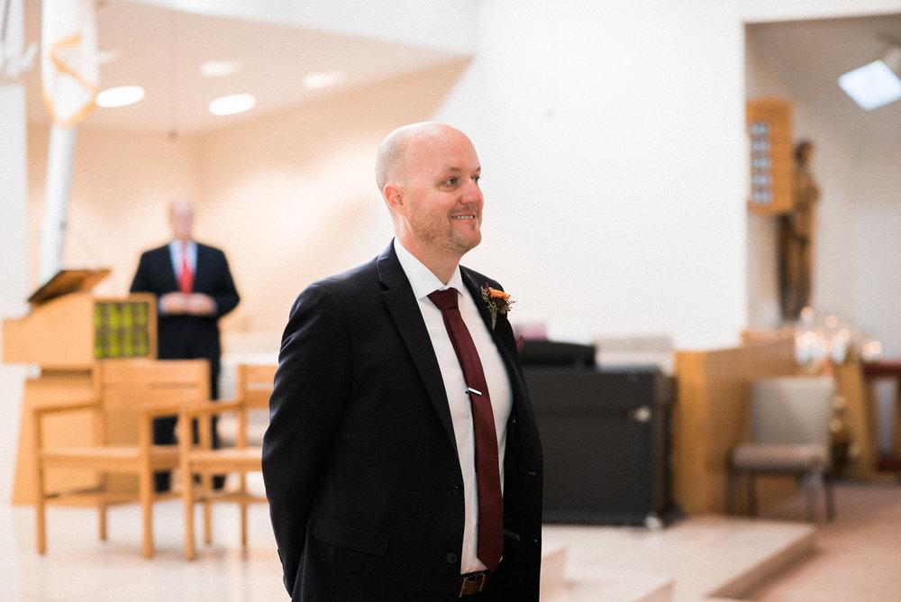 Groom smiling as he sees wife