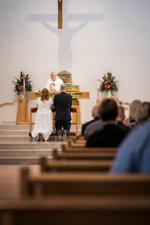 Bride and groom kneeling at altar