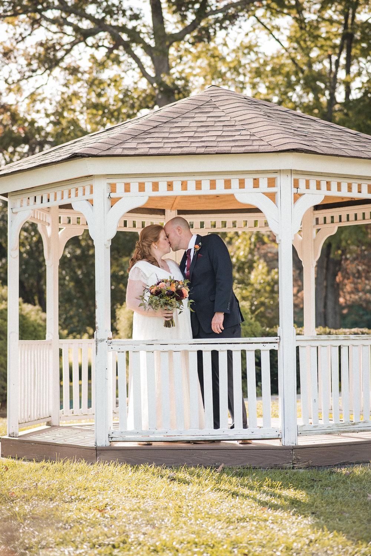 Bride and groom kissing in gazebo