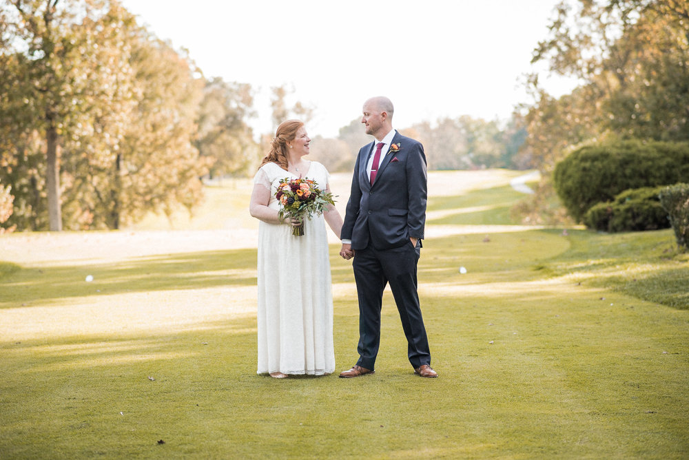 Bride and groom standing on golf course