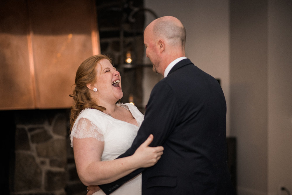 Wife laughing with groom at reception