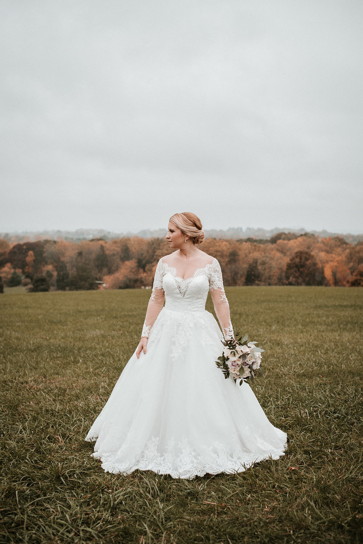 Bride standing alone in field