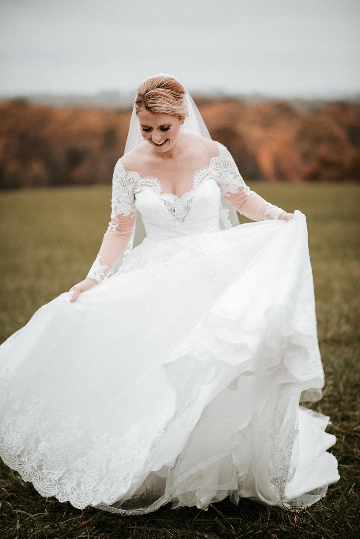 Bride twirling in dress in field