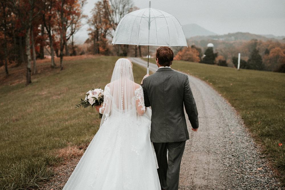 Bride and groom walking away under umbrella