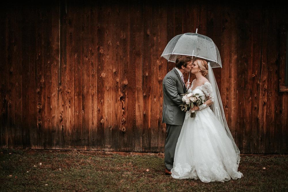 Bride and groom kissing in rain near barn