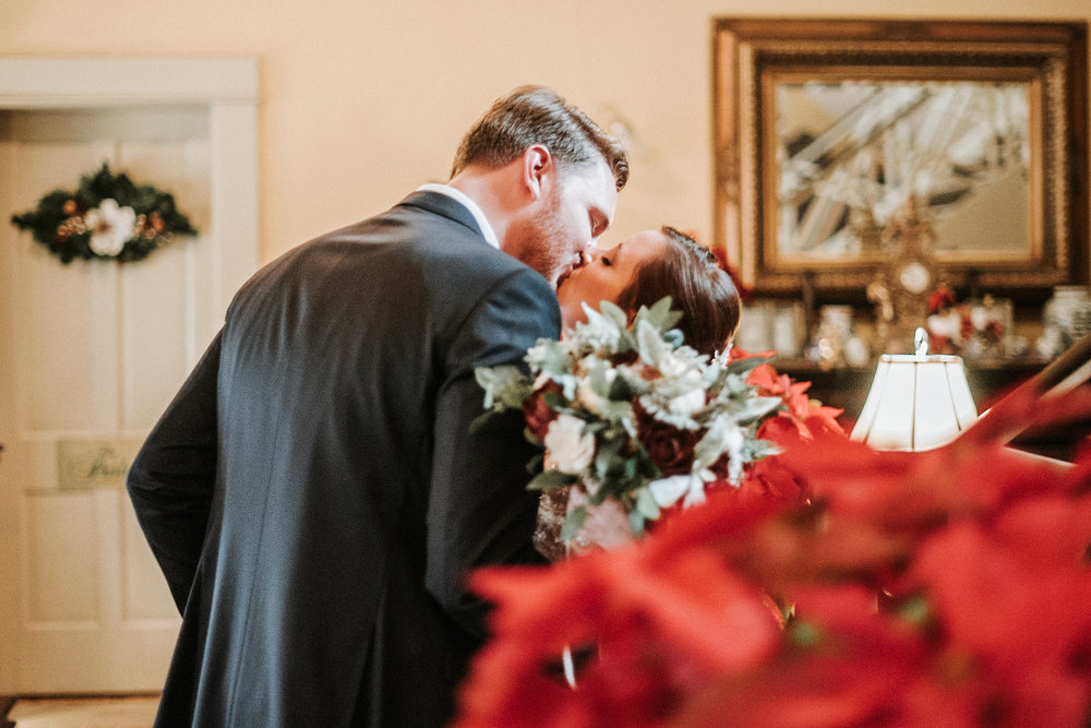 Bride and groom kissing behind flowers