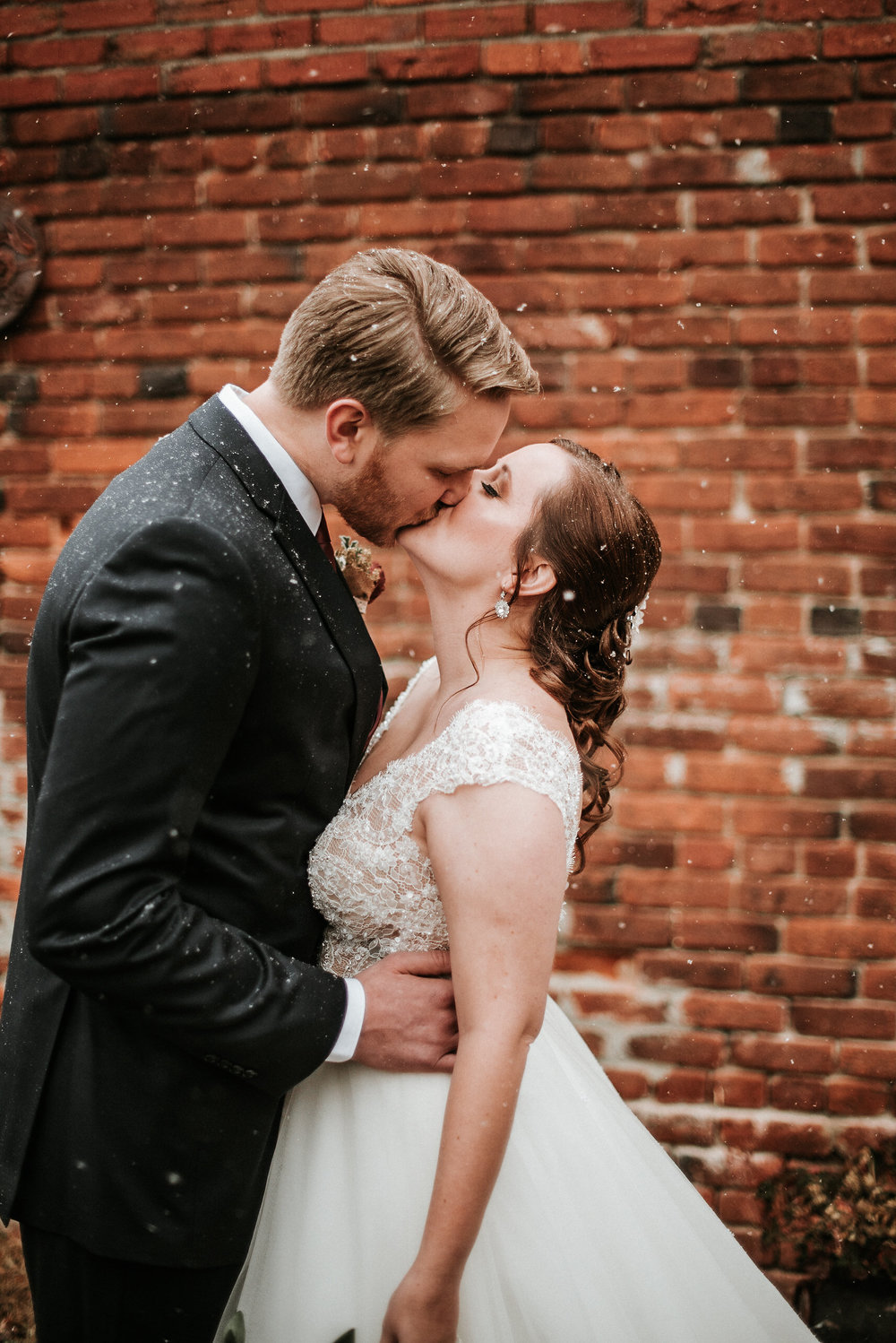 Couple kissing in front of brick wall