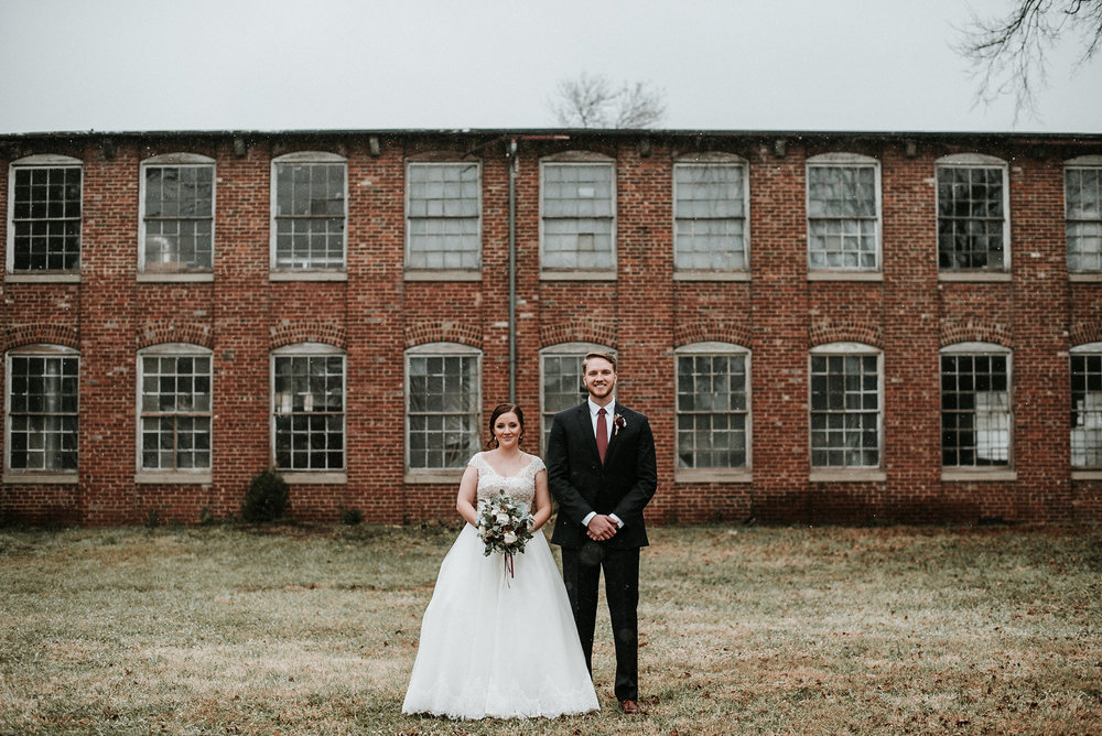 Bride and groom in front of old factory