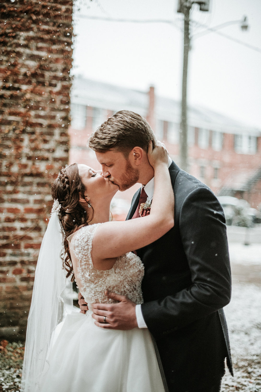 Bride and groom kissing in snow