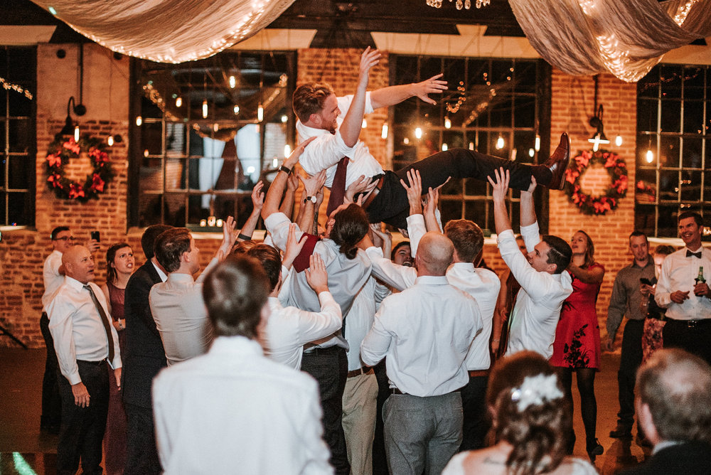 Guests lifting groom