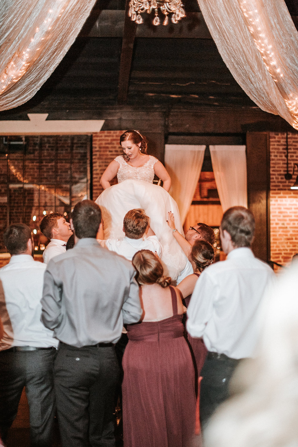 Guests lifting bride on chair