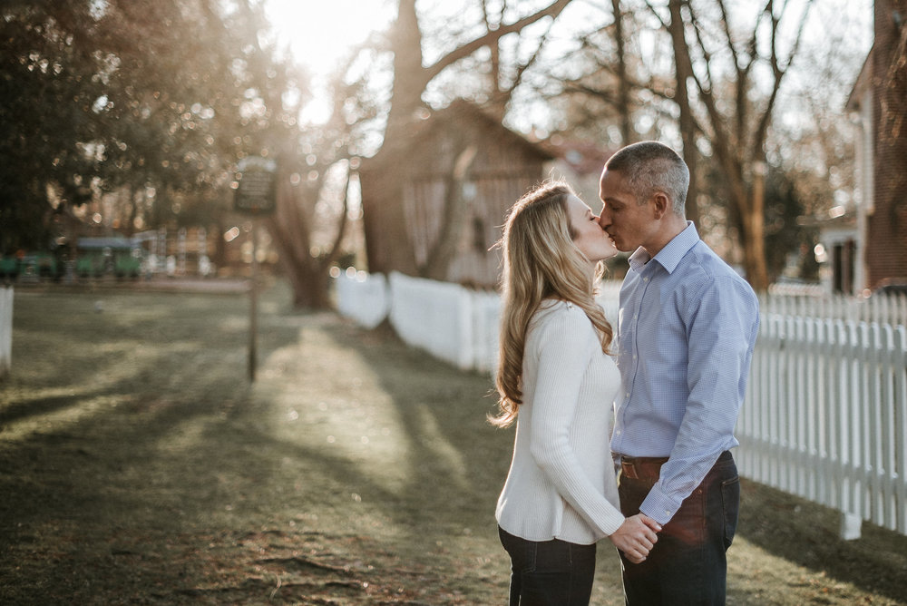 Couple kissing by picket fence