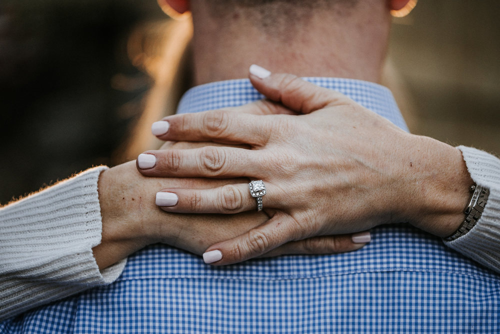 Hands with engagement ring around groom's neck