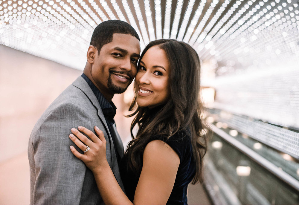 Engaged couple standing in lighted tunnel