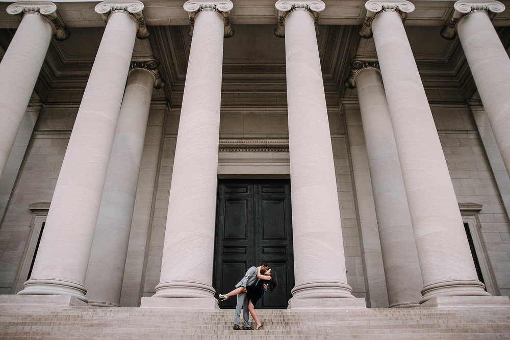 Couple kissing in front of stone columns