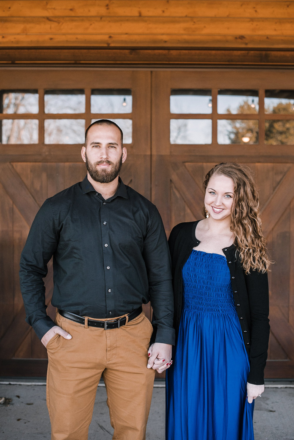 Man and woman holding hands in front of barn door