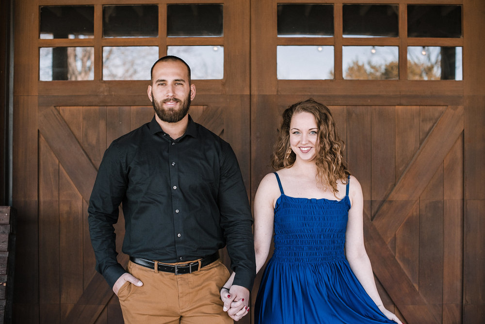 Couple holding hands in front of barn doors