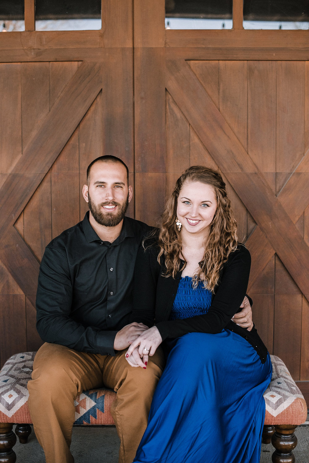 Couple sitting in front of barn doors