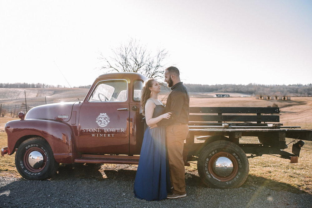 Couple posing in front of farm truck